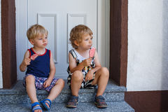 Two little sibling boys eating ice cream. Royalty Free Stock Photo