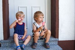 Two little sibling boys eating ice cream. Royalty Free Stock Photos