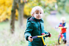 Two little sibling boys having fun on bikes in autumn forest. Royalty Free Stock Photo