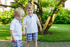Two little sibling boys having fun outdoors in family look Stock Images