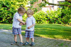 Two little sibling boys having fun outdoors in family look Royalty Free Stock Photo