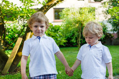 Two little sibling boys having fun outdoors in family look stock photos