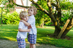 Two little sibling boys having fun outdoors in family look Stock Image