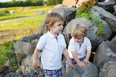 Two little sibling boys having fun outdoors in family look Stock Photography