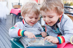 Two little sibling boys having fun together with tablet pc. stock images