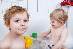 Two little sibling boys having fun with water by taking bath in Stock Photography
