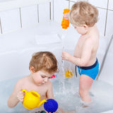 Two little sibling boys having fun with water by taking bath in Royalty Free Stock Image