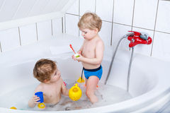 Two little sibling boys having fun with water by taking bath in Stock Photos