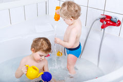 Two little sibling boys having fun with water by taking bath in Royalty Free Stock Photo