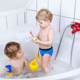 Two little sibling boys having fun with water by taking bath in Royalty Free Stock Photos