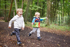 Two little sibling boys having fun with yellow foliage in autumn Royalty Free Stock Photos