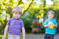 Two little sibling boys hugging and having fun outdoors Stock Photos