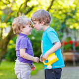 Two little sibling boys hugging and having fun outdoors. Two little happy kid boys hugging and having fun outdoors, in home's garden. Funny friends playing Stock Photo