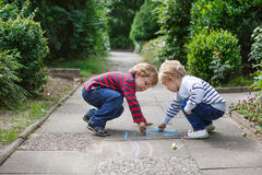 Two little sibling boys painting with chalk outdoors. In summer Stock Image