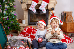 Two little sibling boys playing with christmas toys Stock Photos