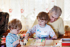 Two little sibling boys playing with grandfather board game. Indoors Stock Images