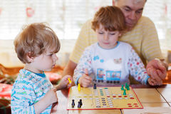 Two little sibling boys playing with grandfather board game Royalty Free Stock Photos