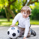 Two little sibling boys playing soccer and football Royalty Free Stock Image