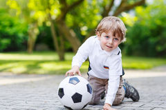 Two little sibling boys playing soccer and football Stock Photos