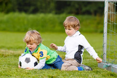 Two little sibling boys playing soccer and football Royalty Free Stock Photo