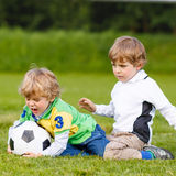 Two little sibling boys playing soccer and football Stock Photo
