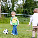 Two little sibling boys playing soccer and football Stock Image