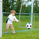 Two little sibling boys playing soccer and football on field Royalty Free Stock Image