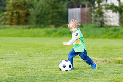 Two little sibling boys playing soccer and football on field Royalty Free Stock Photos