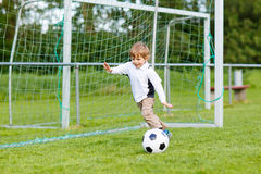 Two little sibling boys playing soccer and football on field Stock Images