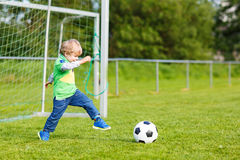 Two little sibling boys playing soccer and football on field Royalty Free Stock Images