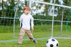Two little sibling boys playing soccer and football on field Stock Photo