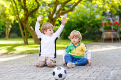 Two little sibling boys playing soccer and football Stock Photography