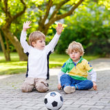 Two little sibling boys playing soccer and football Royalty Free Stock Photos