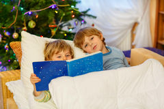 Two little sibling boys reading book on Christmas. Two adorable little blond kid boys, twins reading a book together in bed near Christmas tree with lights and Stock Photo