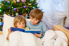 Two little sibling boys reading book on Christmas. Two little blond sibling boys reading a book together in bed near Christmas tree with lights and illumination Stock Photos