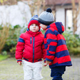 Two little sibling boys in red jackets and winter hats talking t Royalty Free Stock Photo