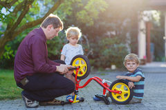 Two little sibling  boys repairing bicycle wheel with father Royalty Free Stock Photography