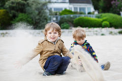 Two little sibling boys sitting on beach of river Elbe and playi Royalty Free Stock Image