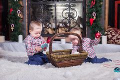 Two little sibling boys sitting by a fireplace royalty free stock images