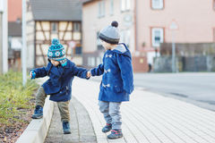 Two little sibling boys walking on the street in German village. Stock Photography