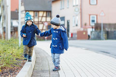 Two little sibling boys walking on the street in German village. Royalty Free Stock Photography
