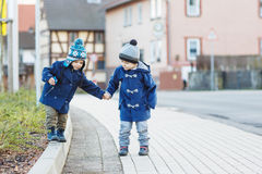 Two little sibling boys walking on the street in German village. Royalty Free Stock Photo