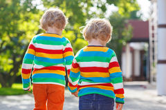 Two little sibling children in colorful clothing walking hand in Royalty Free Stock Image
