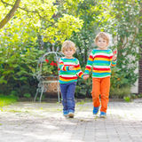 Two little sibling kid boys in colorful clothing Royalty Free Stock Photo