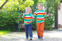 Two little sibling kid boys in colorful clothing walking hand in Royalty Free Stock Image