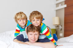 Two little sibling kid boys and dad having fun in bed after slee. Two little sibling kid boys and their dad having fun in bed after sleeping at home, indoor stock photography