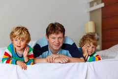 Two little sibling kid boys and dad having fun in. Two little sibling kid boys and their dad having fun in bed after sleeping at home, indoor. Brothers and Royalty Free Stock Photo