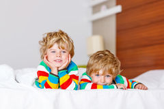 Two little sibling kid boys having fun in bed after sleeping Royalty Free Stock Images