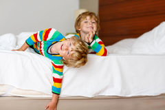 Two little sibling kid boys having fun in bed after sleeping Stock Image
