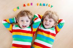 Two little sibling kid boys having fun together, indoors Stock Photos